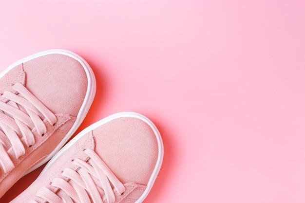 Weibliche rosa turnschuhe auf einer rosa hintergrundnahaufnahme, draufsicht, kopienraum