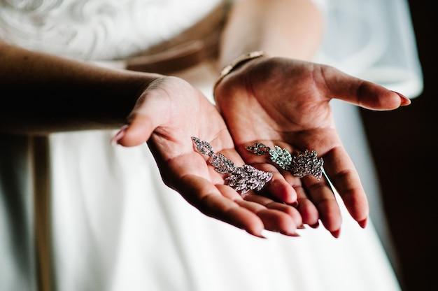 Weibliche schätze ohrring in weiblichen händen