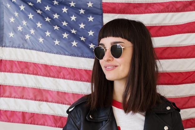 Weibliche schöne frau oder teenager-mädchen trägt neue sonnenbrillenbrille vor amerikanischer flagge, trendiger und modischer hipster, patriot der usa