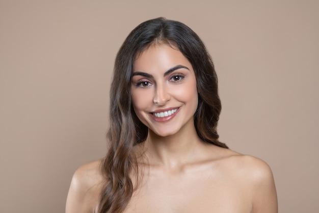 Weibliche schönheit. lächelnde schöne junge erwachsene frau mit nackten schultern in großer stimmung auf hellem hintergrund