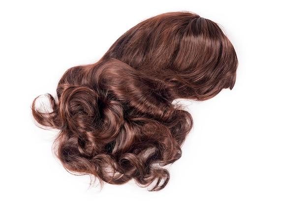 Weibliche schokoladenbraune perücke lokalisiert auf weißem hintergrund. goldbraune echthaargewebe, extensions und perücken. schönheitskonzept der frau.