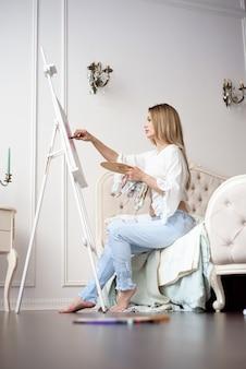 Weibliche schwangere malerin, die im kunststudio unter verwendung der staffelei zeichnet. porträt einer jungen pragmatischen frau, die mit ölfarben auf weißer leinwand malt, seitenansichtporträt