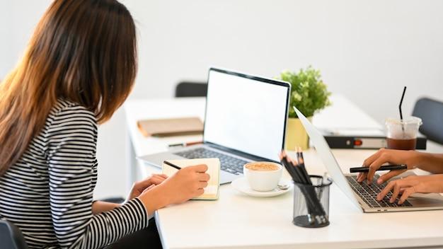 Weibliche sekretärin, die e-mails auf dem laptop überprüft, die arbeit organisiert und notizen macht laptop-modell