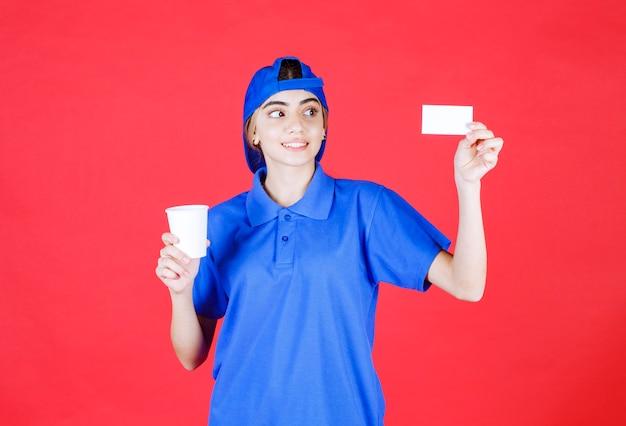 Weibliche service-agentin in blauer uniform, die eine tasse getränk hält und ihre visitenkarte präsentiert.