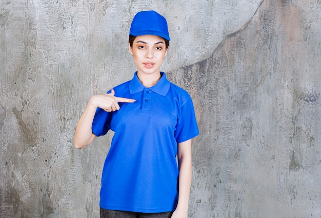 Weibliche servicemitarbeiterin in blauer uniform, die auf sich selbst zeigt.