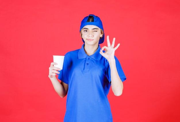 Weibliche servicemitarbeiterin in blauer uniform, die eine einweg-tasse getränk hält und den geschmack genießt. Kostenlose Fotos