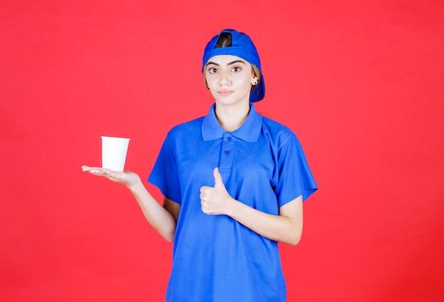 Weibliche servicemitarbeiterin in blauer uniform, die eine einweg-tasse getränk hält und den geschmack genießt.