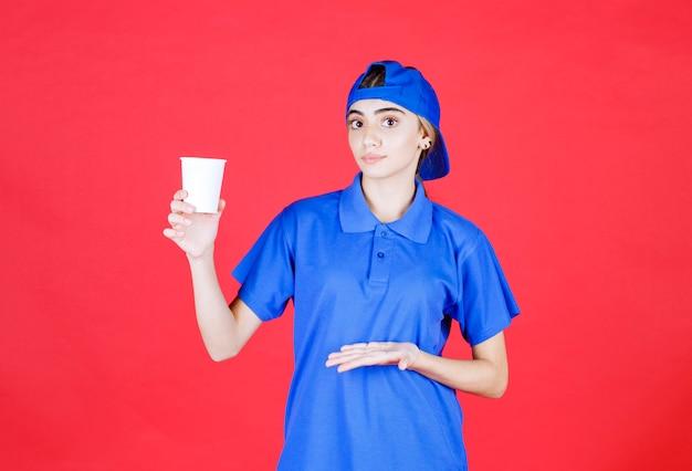 Weibliche servicemitarbeiterin in blauer uniform, die eine einwegschale des getränks hält.