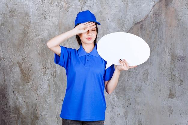 Weibliche servicemitarbeiterin in blauer uniform, die eine ovale infotafel hält und müde aussieht.