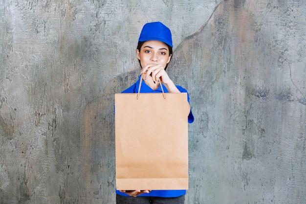 Weibliche servicemitarbeiterin in blauer uniform, die eine papiertüte hält und dem kunden übergibt.