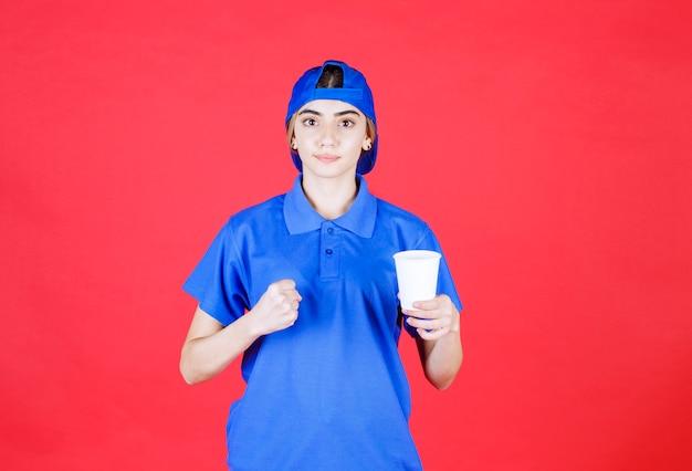 Weibliche servicemitarbeiterin in blauer uniform, die eine tasse einweggetränk hält und ihre faust zeigt.