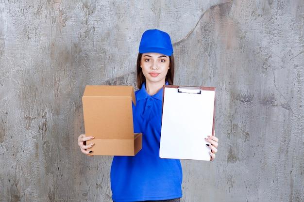 Weibliche servicemitarbeiterin in blauer uniform, die einen offenen karton hält und die unterschriftenliste präsentiert.