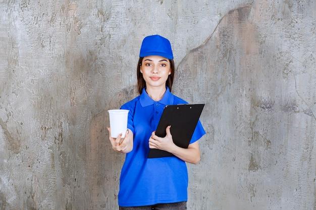 Weibliche servicemitarbeiterin in blauer uniform, die einen weißen einwegbecher und eine schwarze kundenmappe hält.
