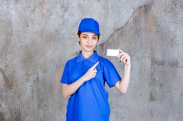 Weibliche servicemitarbeiterin in blauer uniform, die ihre visitenkarte präsentiert.