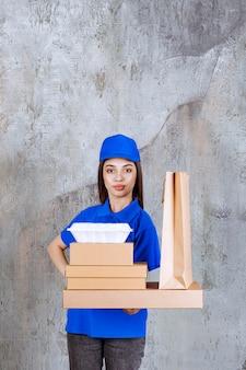 Weibliche servicemitarbeiterin in blauer uniform, die kartons, taschen und kisten zum mitnehmen hält.