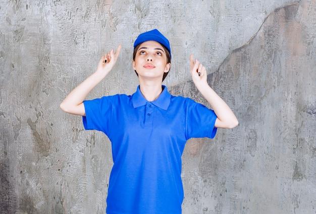 Weibliche servicemitarbeiterin in blauer uniform, die nach oben zeigt.