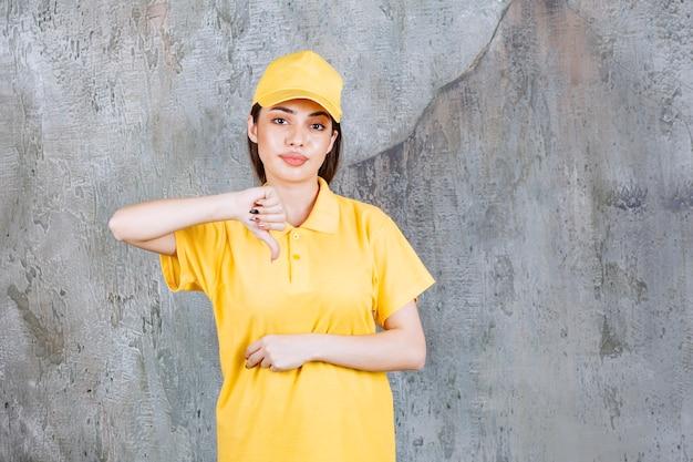 Weibliche servicemitarbeiterin in gelber uniform, die auf betonmauer steht und daumen nach unten zeigt.