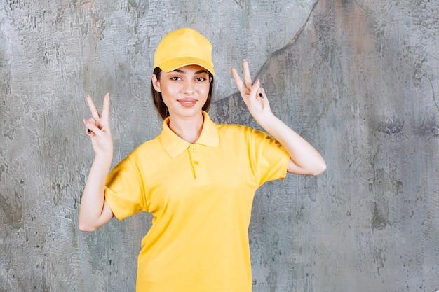 Weibliche servicemitarbeiterin in gelber uniform, die auf betonmauer steht und frieden sendet.