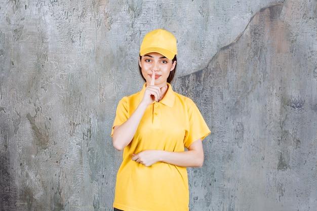 Weibliche servicemitarbeiterin in gelber uniform, die auf betonmauer steht und um stille bittet.
