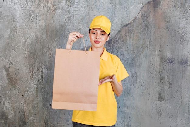Weibliche servicemitarbeiterin in gelber uniform, die eine einkaufstasche hält und sie dem kunden präsentiert.