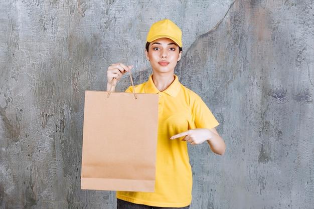Weibliche servicemitarbeiterin in gelber uniform, die eine papiertüte hält.