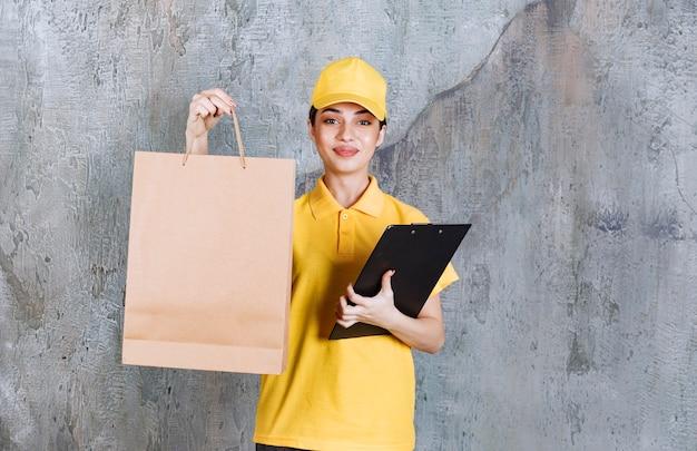 Weibliche servicemitarbeiterin in gelber uniform, die eine papiertüte und eine schwarze adressliste hält.