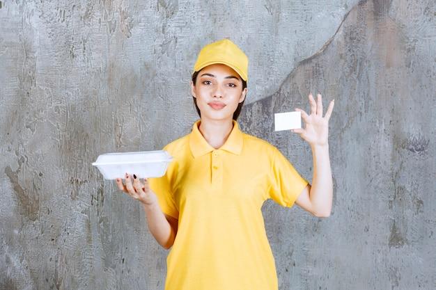 Weibliche servicemitarbeiterin in gelber uniform, die eine plastikbox zum mitnehmen hält und ihre visitenkarte vorlegt