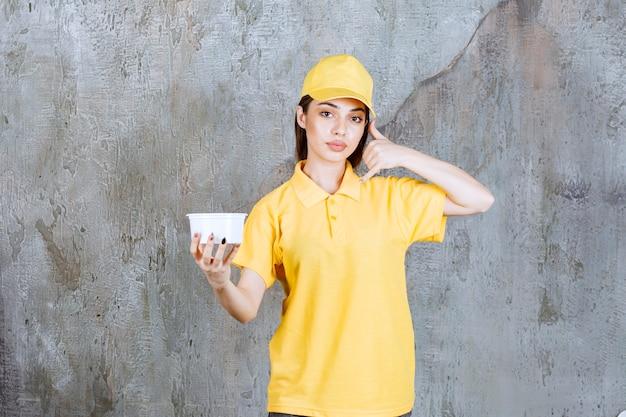 Weibliche servicemitarbeiterin in gelber uniform, die eine plastikschüssel zum mitnehmen hält und um einen anruf bittet.