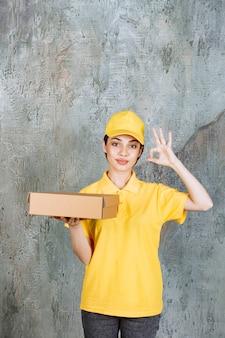 Weibliche servicemitarbeiterin in gelber uniform, die einen karton hält und ein positives handzeichen zeigt.