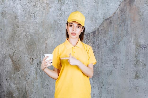 Weibliche servicemitarbeiterin in gelber uniform, die einen plastikbecher hält.