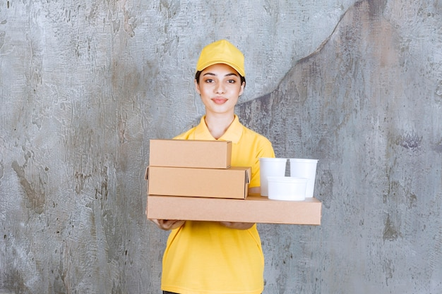 Weibliche servicemitarbeiterin in gelber uniform, die einen vorrat an pappkartons und plastikbechern zum mitnehmen hält.