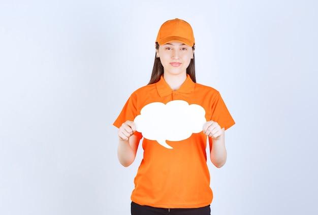 Weibliche servicemitarbeiterin in orangefarbenem dresscode, die eine infotafel in wolkenform hält