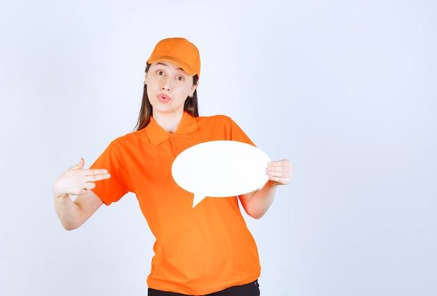 Weibliche servicemitarbeiterin in orangefarbenem dresscode, die eine ovale infotafel hält und überrascht und verängstigt aussieht