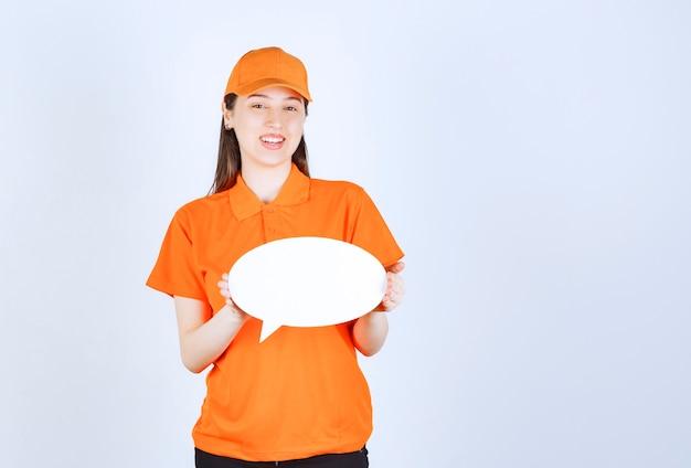 Weibliche servicemitarbeiterin in orangefarbenem dresscode, die eine ovale infotafel hält