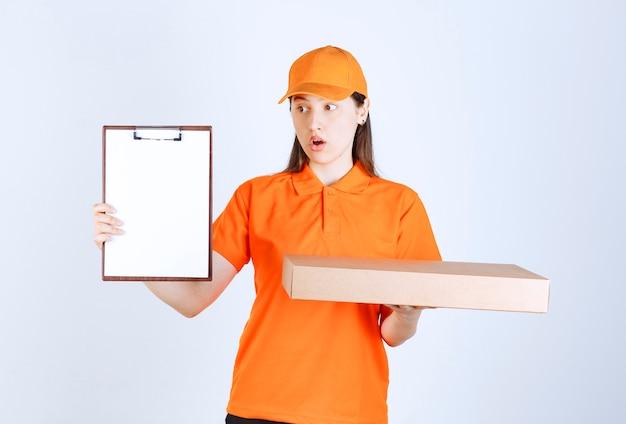 Weibliche servicemitarbeiterin in orangefarbenem dresscode, die eine pizzaschachtel zum mitnehmen aus pappe hält und um unterschrift bittet, während sie verwirrt aussieht