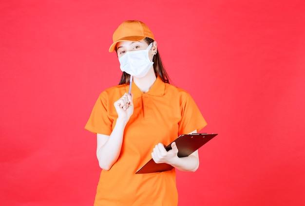 Weibliche servicemitarbeiterin in orangefarbenem dresscode und maske, die beim nachdenken ein projektblatt und einen stift hält.