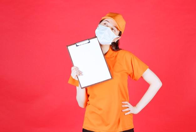 Weibliche servicemitarbeiterin in orangefarbenem dresscode und maske, die das projektblatt demonstriert und nachdenklich aussieht.