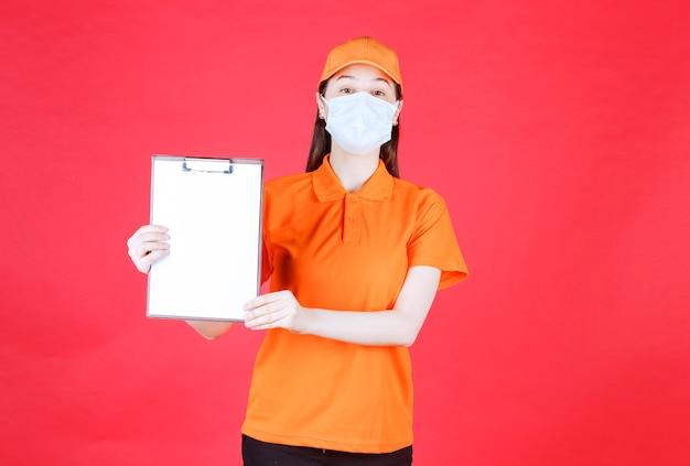 Weibliche servicemitarbeiterin in orangefarbenem dresscode und maske, die das projektblatt zeigt