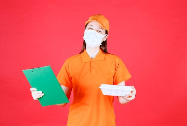 Weibliche servicemitarbeiterin in orangefarbenem dresscode und maske, die ein essenspaket zum mitnehmen hält und den grünen ordner überprüft