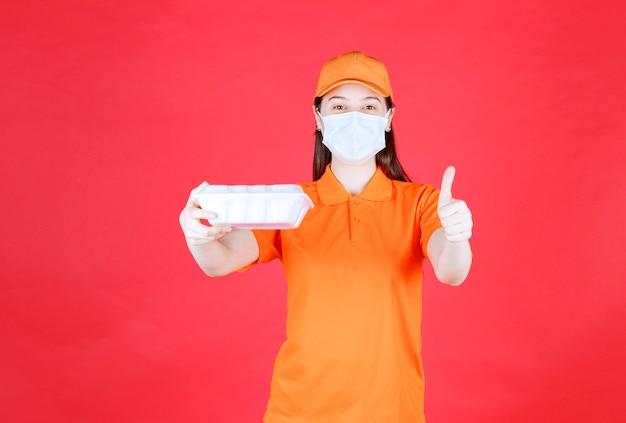 Weibliche servicemitarbeiterin in orangefarbenem dresscode und maske, die ein essenspaket zum mitnehmen hält und ein positives handzeichen zeigt