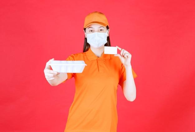 Weibliche servicemitarbeiterin in orangefarbenem dresscode und maske, die ein essenspaket zum mitnehmen hält und ihre visitenkarte vorlegt
