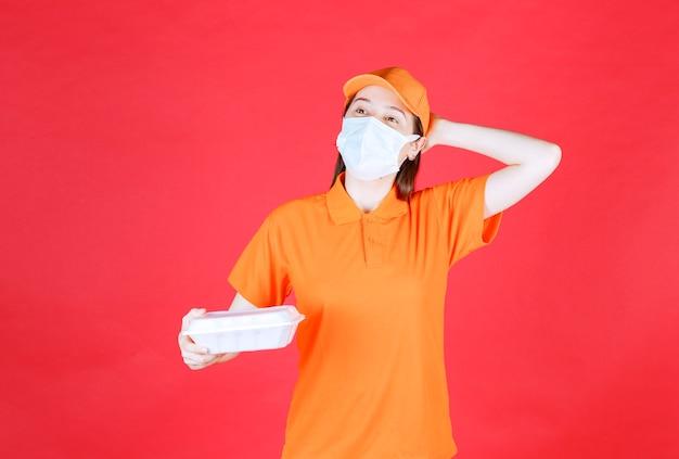 Weibliche servicemitarbeiterin in orangefarbenem dresscode und maske, die ein essenspaket zum mitnehmen hält und nachdenklich und träumend aussieht