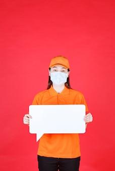Weibliche servicemitarbeiterin in orangefarbenem dresscode und maske, die eine weiße rechteck-infotafel hält