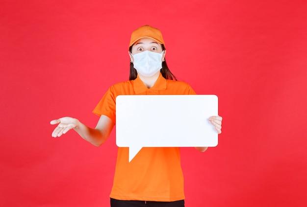 Weibliche servicemitarbeiterin in orangefarbenem dresscode und maske, die eine weiße rechteckige infotafel hält und verwirrt und unsicher aussieht