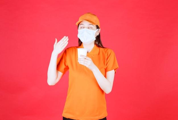 Weibliche servicemitarbeiterin in orangefarbenem dresscode und maske, die einen einwegbecher hält und das produkt riecht.