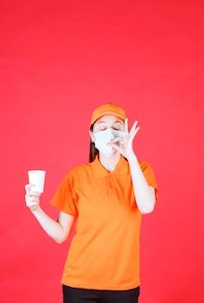 Weibliche servicemitarbeiterin in orangefarbenem dresscode und maske, die einen einwegbecher hält und ein positives handzeichen zeigt