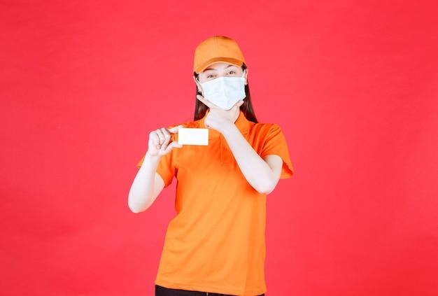 Weibliche servicemitarbeiterin in orangefarbenem dresscode und maske, die ihre visitenkarte präsentiert und verwirrt oder nachdenklich aussieht.