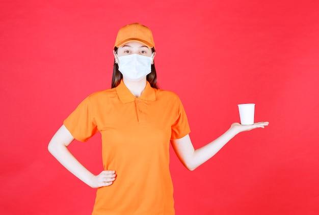 Weibliche servicemitarbeiterin in orangefarbenem dresscode und maske mit einem einwegbecher