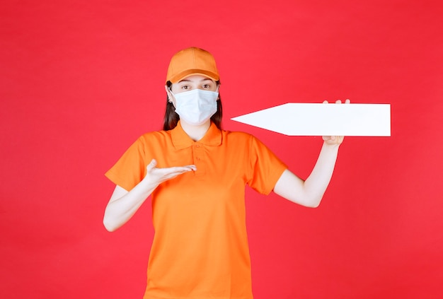 Weibliche servicemitarbeiterin in orangefarbenem dresscode und maske mit einem nach links weisenden pfeil.