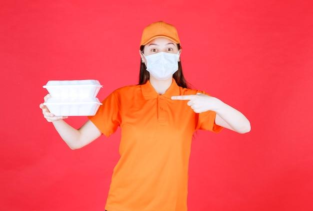 Weibliche servicemitarbeiterin in orangefarbenem dresscode und maske mit zwei essenspaketen zum mitnehmen